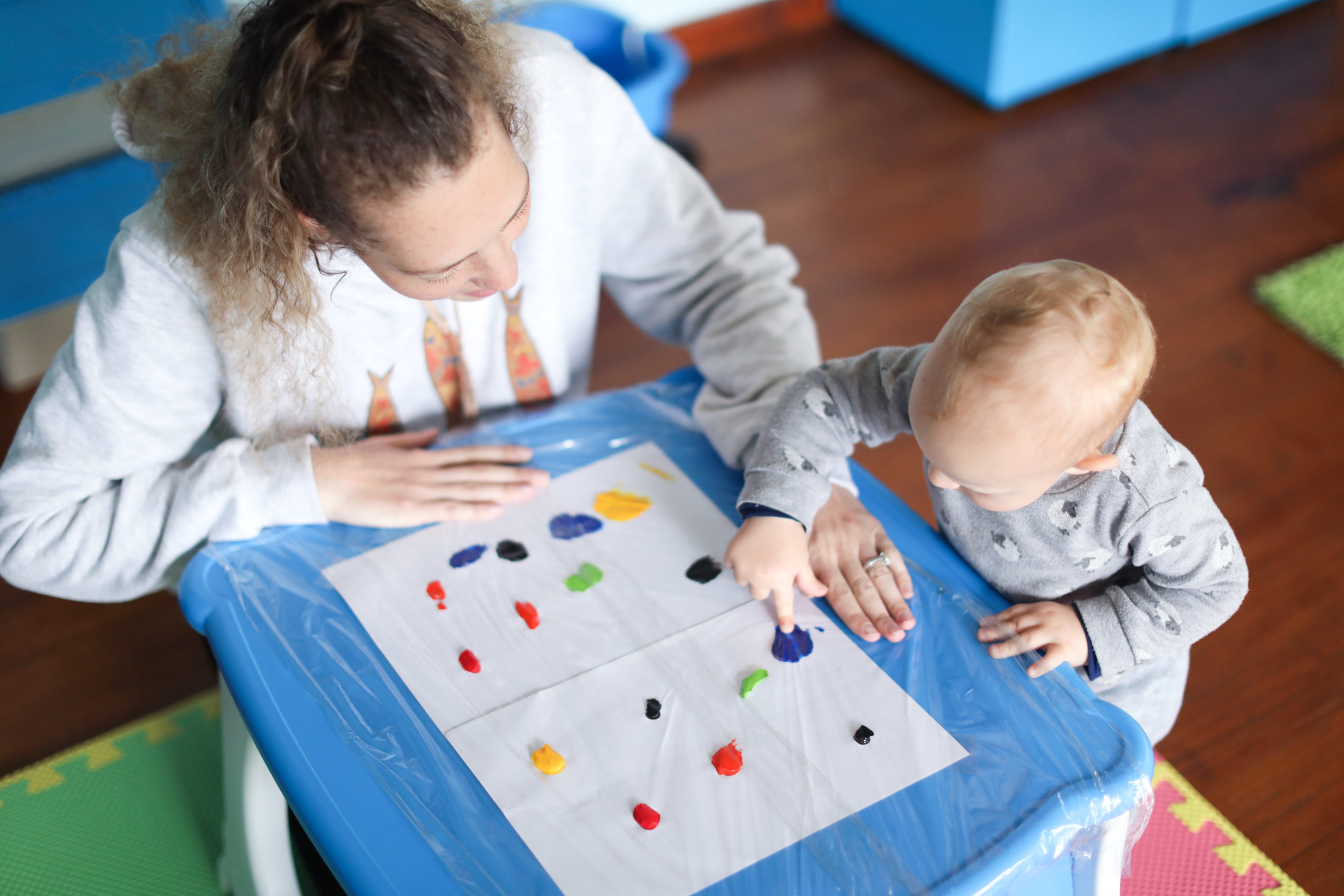 a Baby boy finger painting with his mother.