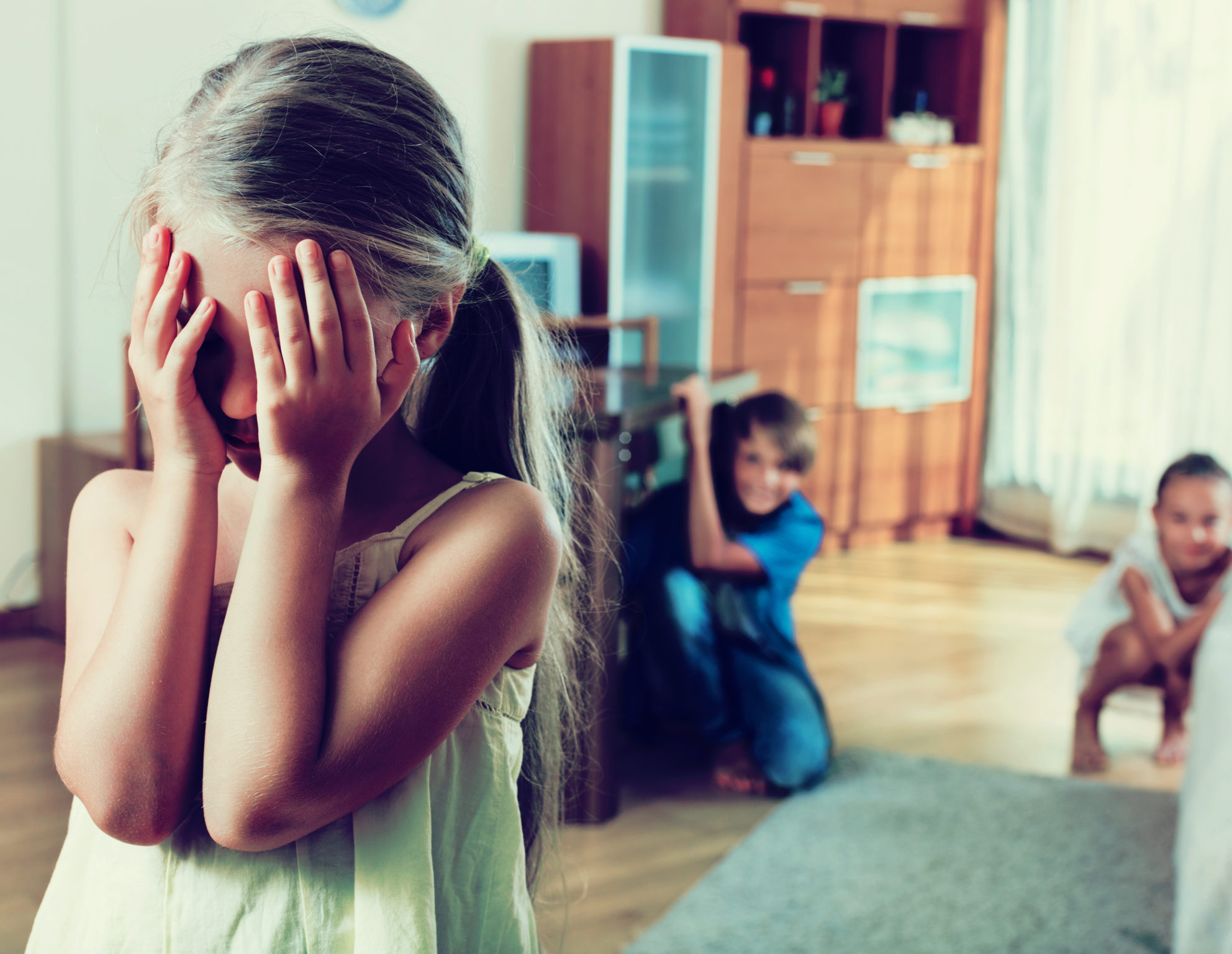 Joyful happy children hiding from girl