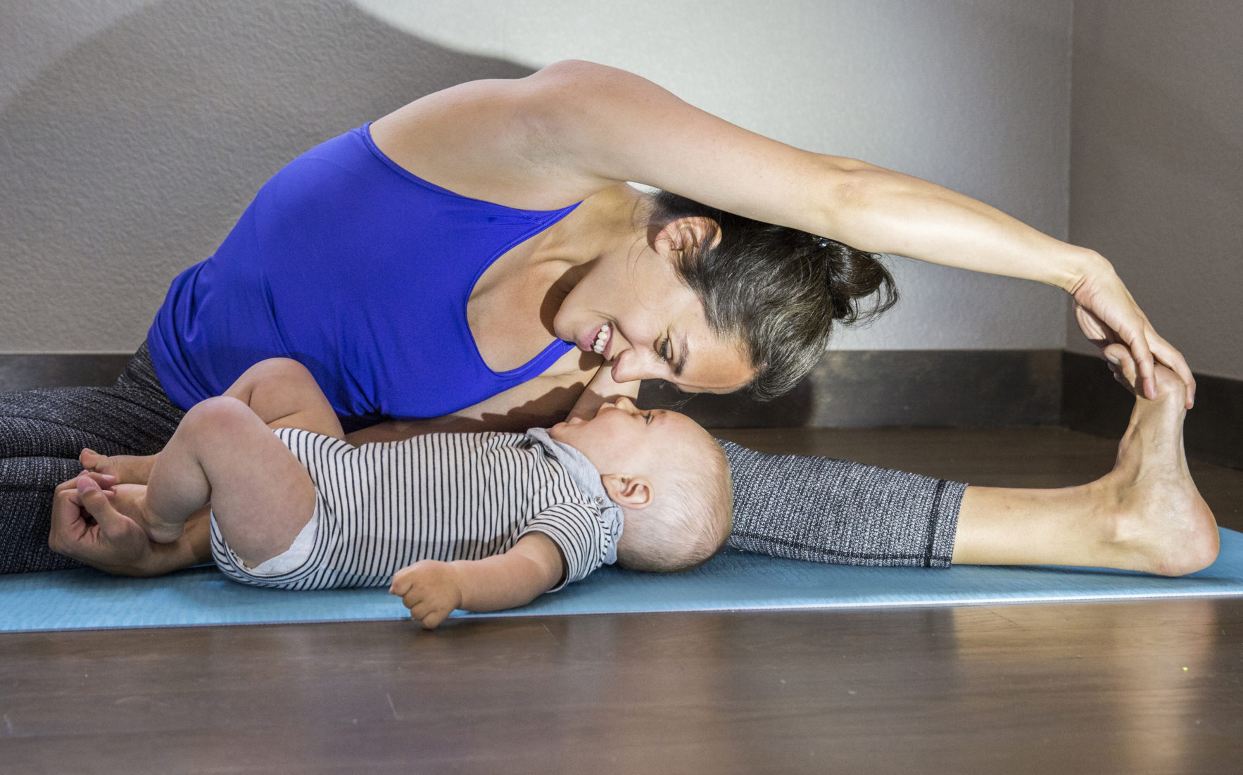 Happy mother stretches while admiring her baby boy